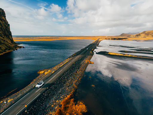 Wide shot of car driving down a road in Iceland as a part of a self-drive tour.